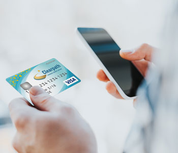 Man holding Clearpath credit card and smartphone